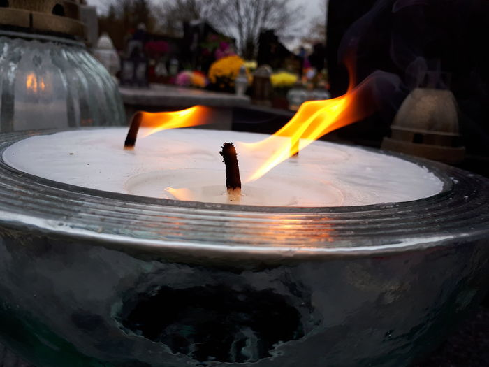 Close-up of lit candles in water
