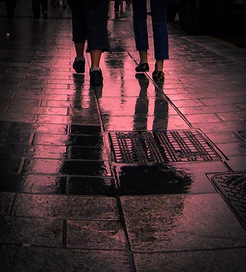 Low section of man standing on wet sidewalk during rainy season