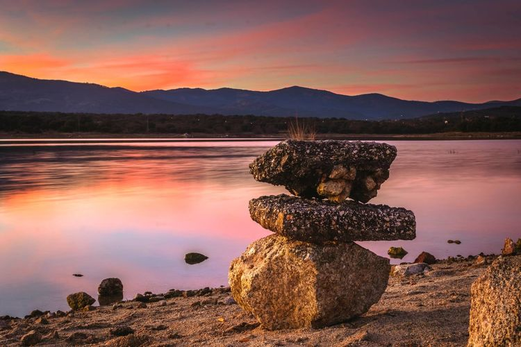 Stacked rocks by lake against sky during sunset