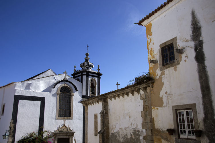 Impressions of the medieval city of Óbidos in Portugal. MedievalTown Obidos Portugal Portugal Architecture Bell Tower Building Exterior Built Structure Clear Sky Cross Day Low Angle View Medieval Castle No People Outdoors Place Of Worship Religion Sky Spirituality Tourism Whitewashed Window Óbidos