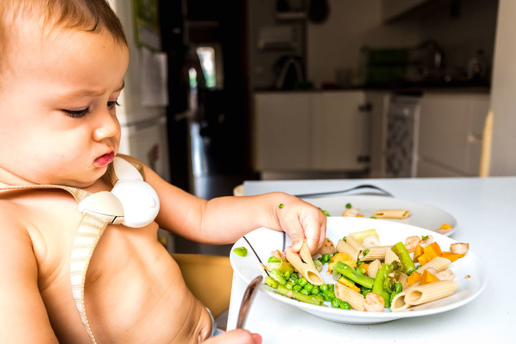 Close-up of baby eating food on table at home