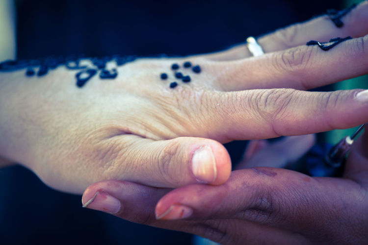 Cropped image of woman with henna tattoo touching friend hand