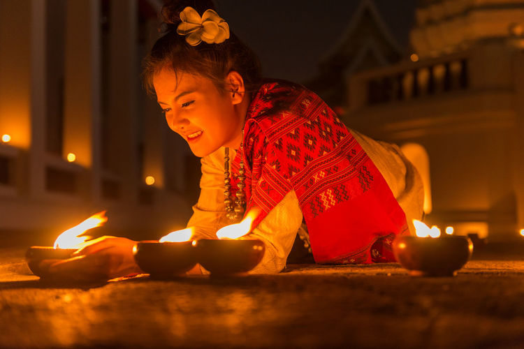 Young woman lighting candles paying the homage to the lord Buddha at Thai temple, Bangkok, Thailand. Candles Loy Krathong Nighttime Thai Festival Tradition Buddhism Burning Celebration Child Childhood Clothing Costume Fire Flame Illuminated Indoors  Lighting Lighting Equipment Night Offspring One Person Religion Temple Thai Culture Traditional Clothing
