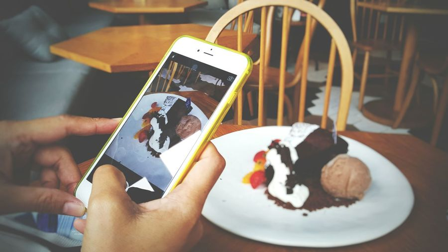 Cropped hands photographing ice cream sundae with smart phone