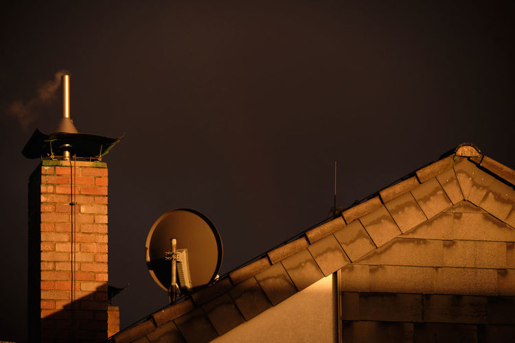 A bricked chimney with some smoke coming out together with some antennas o the roof of a house in the last rays of evening sun in front of a dramatic dark sky of a thunderstorm. Seen in Nuremberg, Germany, in April 2019 Architecture Built Structure Sky Building Exterior No People Night Low Angle View Nature Building Outdoors Communication Technology Europe Germany Nuremberg Nürnberg Thunderstorm Smoke Chimney Sunrays Sunset Storm Cloud Brick Wall Antennas Broadcasting Broadcast Television Sattelite Dish Co2 Emission Nebula Carbonated Dioxide Pollution Heating House Roof Grey Future Dramatic Lighting Equipment Illuminated Street Light Dusk Travel Destinations Copy Space Street