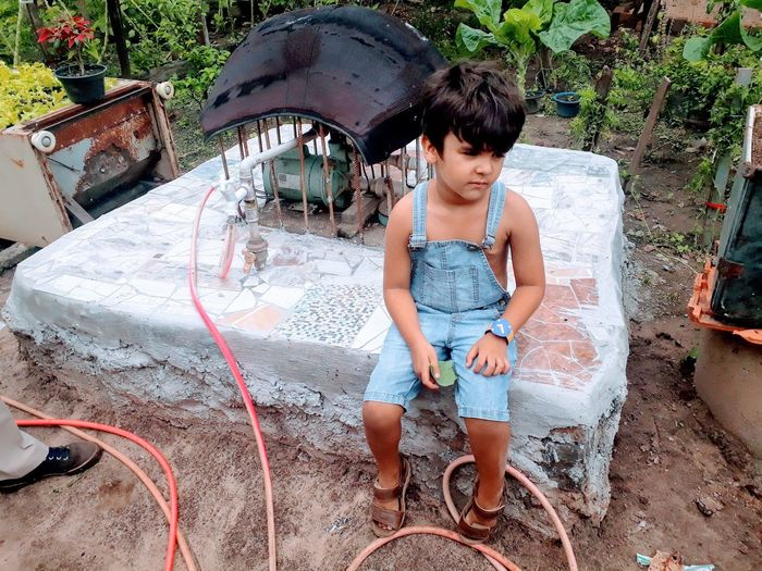High angle view of boy sitting by water pump in yard