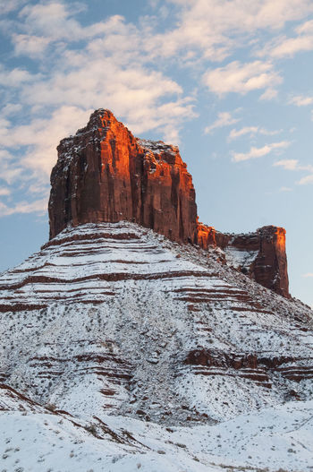 Rock formations on snow covered mountain against sky