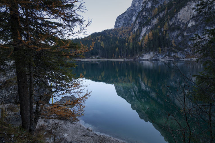Scenic view of lake by trees against sky in dolomites mountains