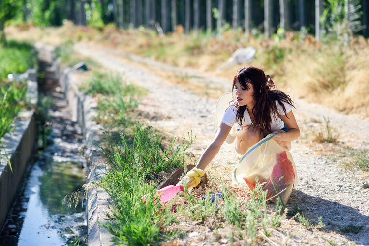 Woman on street amidst plants