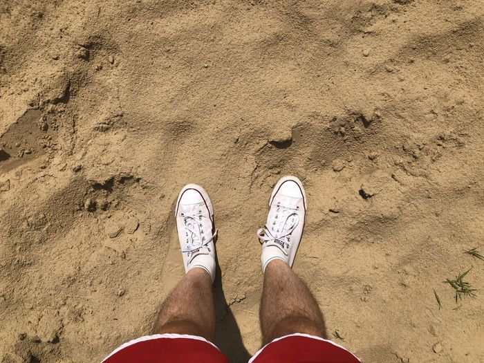 Low section of man standing on sand