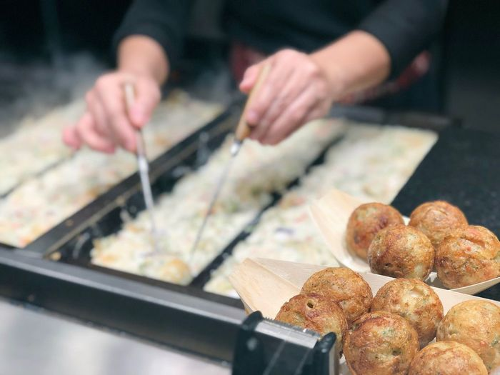 A male hand is making a takoyaki with octopus inside in the shop ready for sell Octopus Japanese Food Japanese  Japan Making Cooking Takoyaki Food Food And Drink Hand Preparation