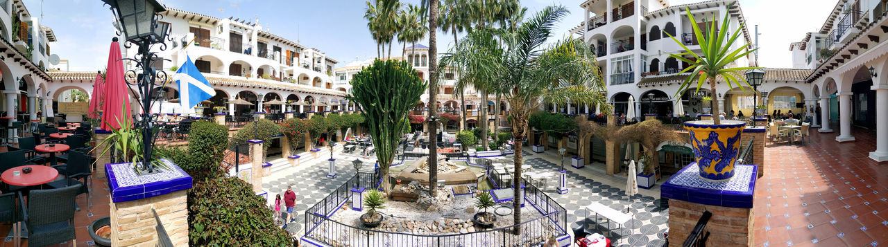 Villamartin, Spain - April 7, 2018: View of Villamartin Plaza. Villamartin Plaza lined with a bars and restaurants. Beautifully landscaped gardens and fountains. Costa Blanca. Spain Bars And Restaurants Costa Blanca Orihuela  Palm Tree Panorama Panoramic Restaurants SPAIN Square Summertime Sunny Vacations Architecture Building Exterior Built Structure Commercial Day Europe Landscaped Outdoors Plant Plaza Springtime Summer Villamartin