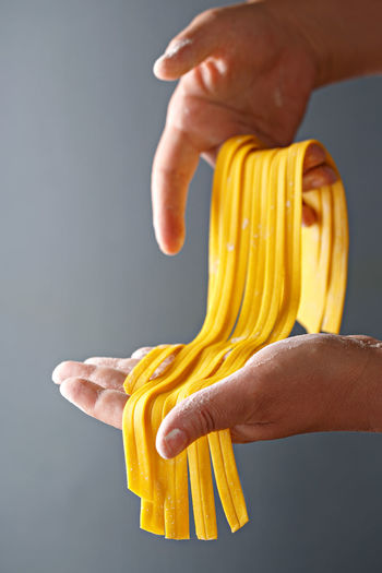 Fresh pasta drying in a woman hands. Woman holding raw tagliatelle on a dark background. Close-up Eggs Food Fresh Pasta Freshness Healthy Eating Holding Human Body Part Human Hand Indoors  Italian Food One Person Pasta Raw Food Tagliatelle Yellow