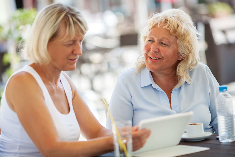 Portrait Of Two Mature Women Sitting At Cafe