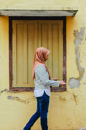 Side view of woman wearing hijab standing against wall
