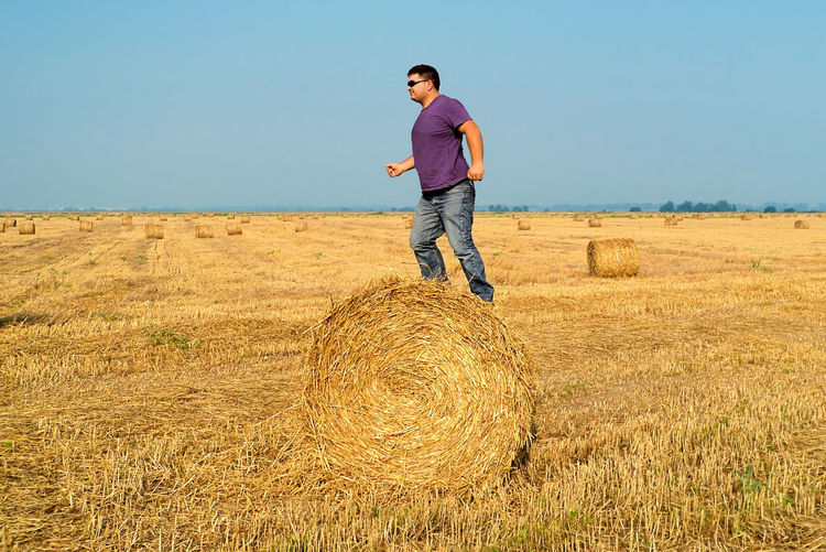 Rolling forward on the hay bale Forward Moving Agriculture Ambition Bale  Casual Clothing Day Environment Farm Field Hay Keep Up Land Landscape Lifestyles Men Nature One Person Outdoors Plant Real People Rolling Sky