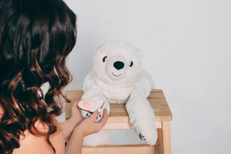 Close-up of woman holding toy against wall