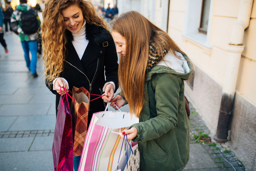 Two young attractive women look at shopping bags Boutique Business Sale Shopping Standing Bag Buying City Consumerism Customer  Gift Lifestyles People Positive Emotion Real People Retail  Santas Hat Shopaholic Shopping Shopping Bag Shopping Mall Store Street Young Adult Young Women