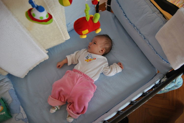 High Angle View Of Baby Lying In Crib At Home