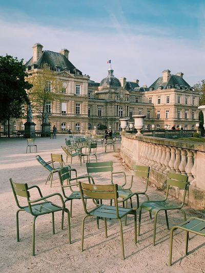 Empty chairs and tables against buildings in city