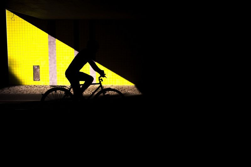 Silhouette man with bicycle on wall