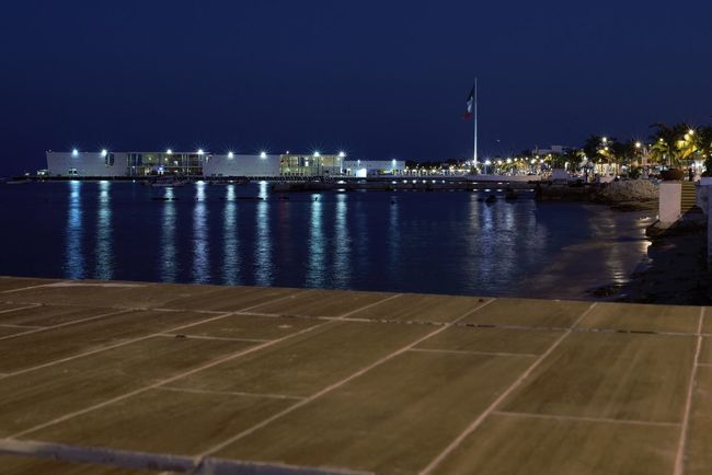 A view of the port of Cozumel at night Night Flag Illuminated Sea Water Architecture Building Exterior No People Built Structure Nature Outdoors Sky Beauty In Nature