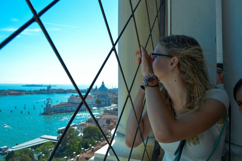 Woman looking through window with santa maria della salute in background