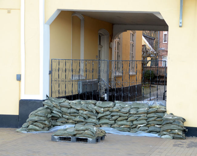 Prepared for the flood, a gate has been blocked by sandbags, the water is approaching. Stack Building Architecture Built Structure No People Door Building Exterior Entrance Large Group Of Objects Wood - Material Day Abundance Business Wall - Building Feature Furniture Flooring Outdoors Wood Domestic Room Gate Sea Weather Sandbags Storm Surge Water