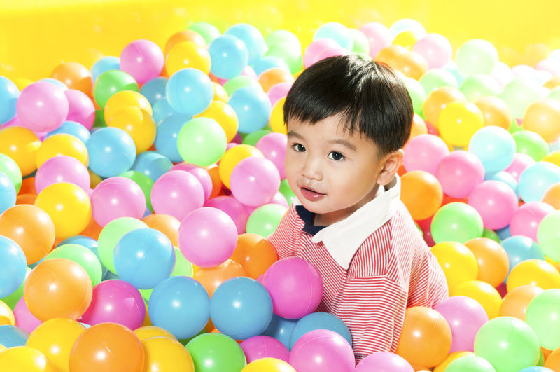 Smiling boy sitting in colorful ball pool