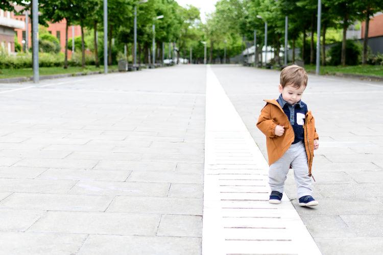 Full length of boy walking on footpath in city