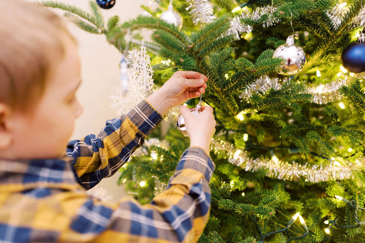 Midsection of boy with christmas tree