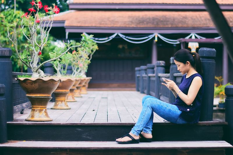Asian girl using smart phone while sitting on wooden floor in Thai house. Sitting Lifestyles Wireless Technology Outdoors Portable Information Device Young Women Architecture Thailand Art And Craft Traditional Culture Travel Destinations Countryside Building Exterior Wood - Material Leisure Activity Asian  Pretty Beautiful Girl Smart Phone Communication Connection Business Social Media The Week On EyeEm