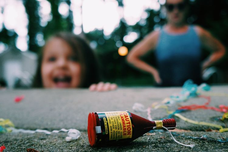 Close-up of firework in bottle on retaining wall with people in background