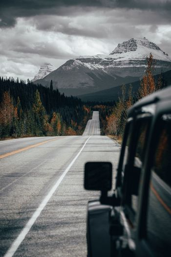 Road leading towards mountains seen through car window