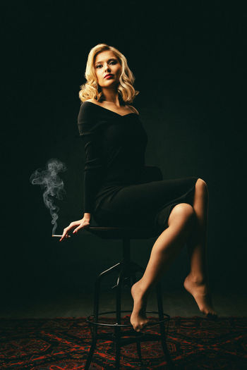 Portrait of young woman sitting with cigarette on stool