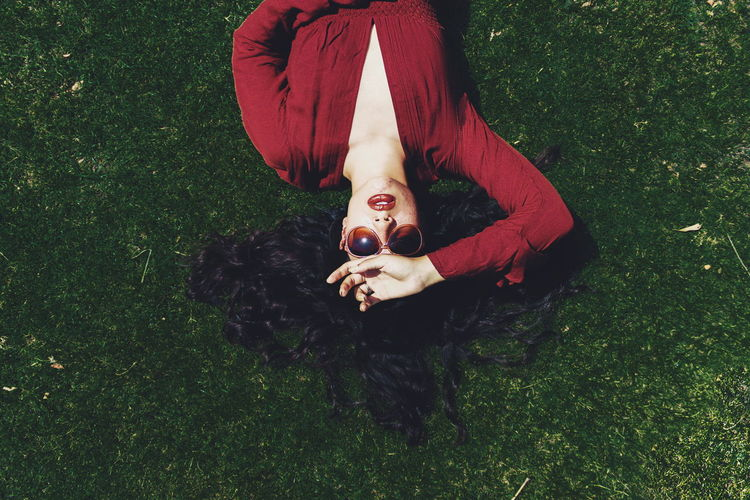High angle view of young woman lying on grassy field