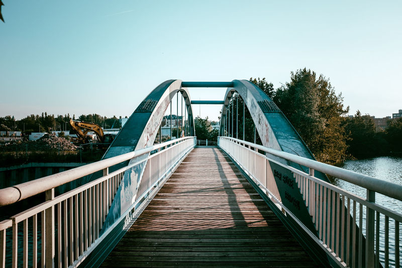 Bridge to the upcoming European quarter Architecture Blue Boardwalk Bridge Bridge - Man Made Structure Built Structure Clear Sky Connection Day Diminishing Perspective Engineering Footbridge Long Nature No People Outdoors Railing Sky The Street Photographer - 2016 EyeEm Awards The Way Forward Tranquil Scene Tranquility Tree Vanishing Point Walkway