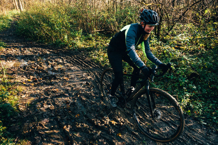Man riding bicycle on field in forest