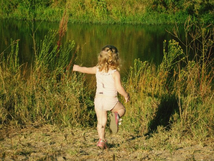 Girl playing beside river