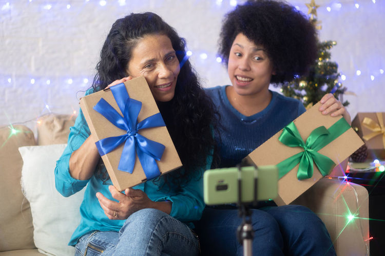 Mother and daughter showing gift box while video conferencing