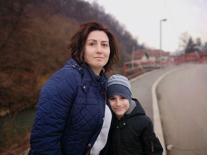 Portrait of mother and son standing in city