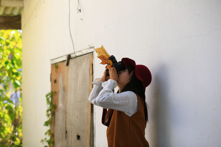 Side view of woman photographing with leaf on camera