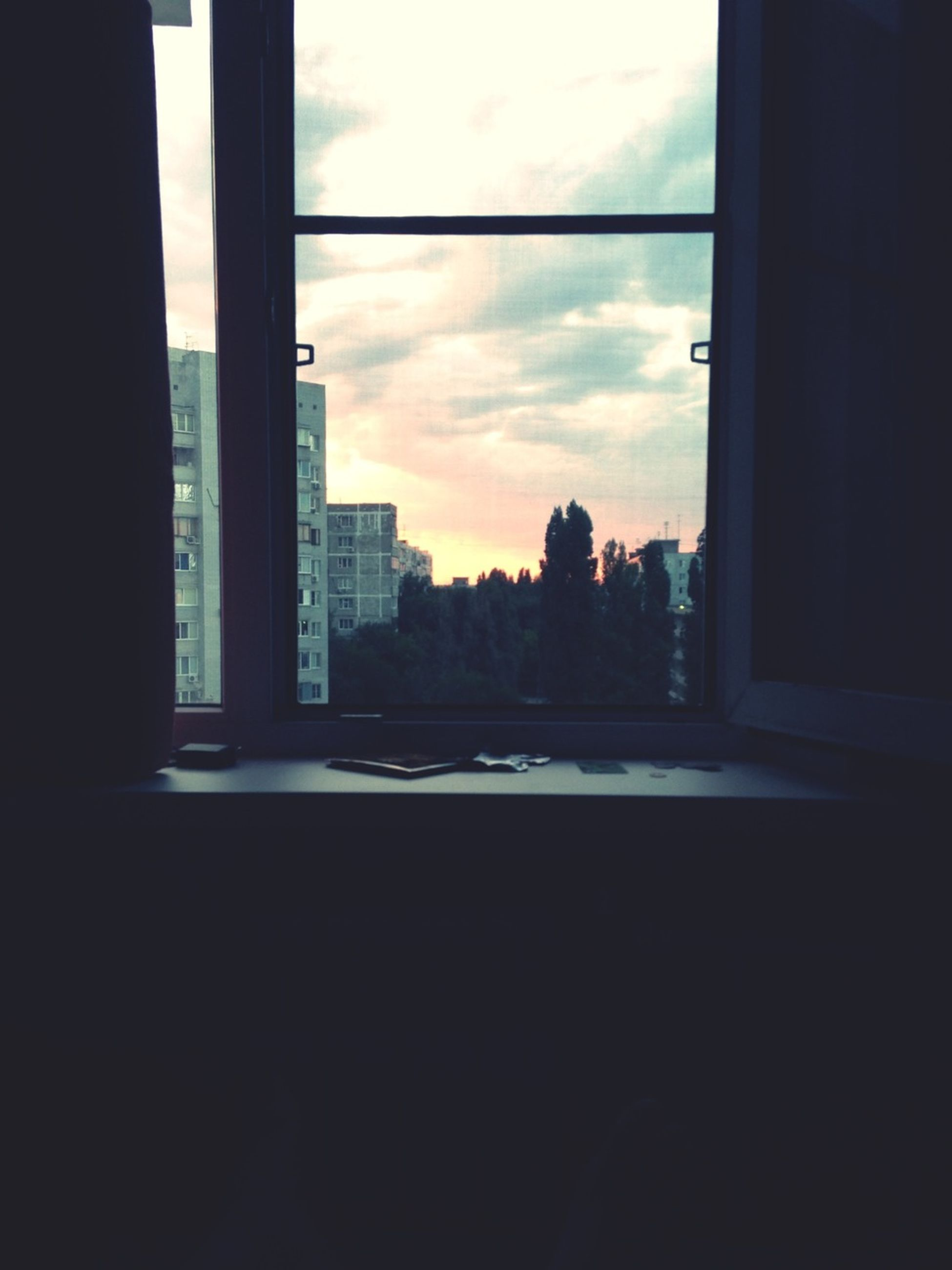window, architecture, sky, built structure, silhouette, indoors, glass - material, building exterior, transparent, dark, cloud - sky, sunset, cloud, looking through window, city, sunlight, no people, building, tree, house