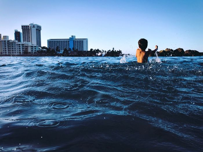 Rear view of boy in river against clear sky