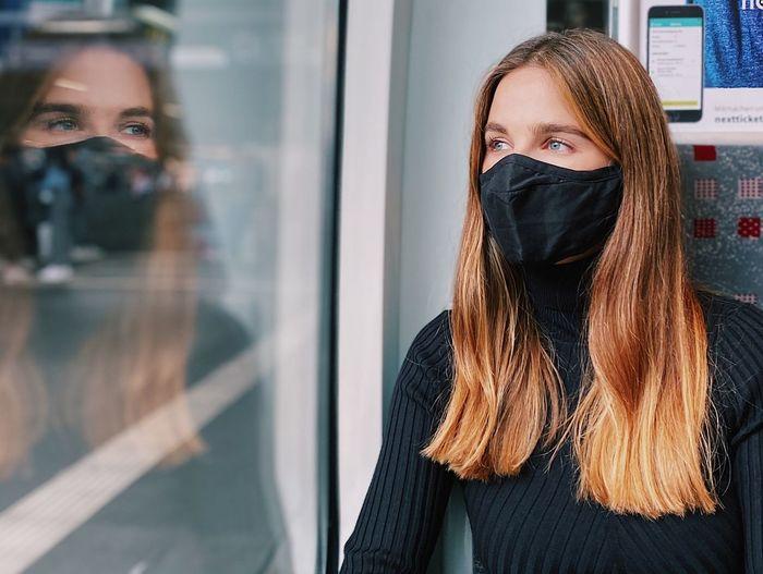 Woman wearing mask looking through glass window