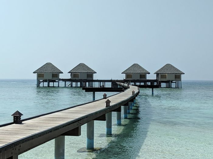 Stilt houses on pier by sea against clear sky