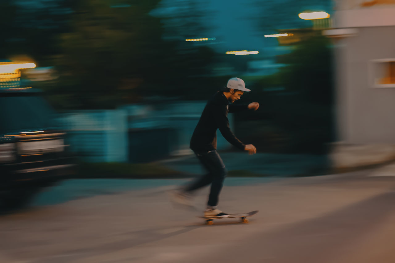 motion, full length, blurred motion, speed, night, lifestyles, skill, real people, one person, balance, leisure activity, city, outdoors, illuminated, healthy lifestyle, ice-skating, sport, ice rink, people