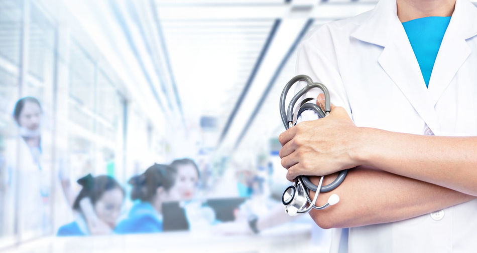 Adult Background Blue Blur Blurred Care Caucasian Clinic Closeup Concept Doctor  Emergency Fingers Hand Health Health Care Holding Hospital Human Interior Male Medic  Medical Medicine Occupation Patient People person Physician Practitioner Professional Screening Space Specialist Standing Stethoscope  Uniform White Woman Work Young Focus On Foreground Indoors  Healthcare And Medicine Medical Equipment Medical Instrument Clothing Lab Coat