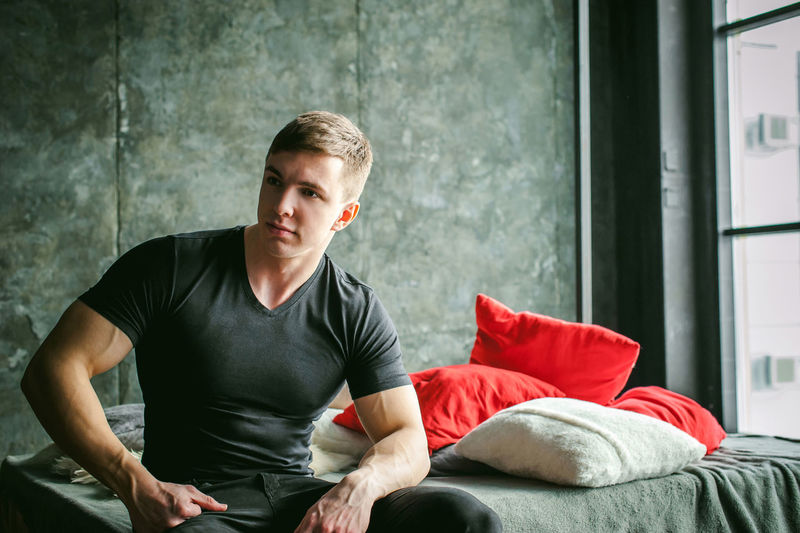 Muscular man sitting on bed at home