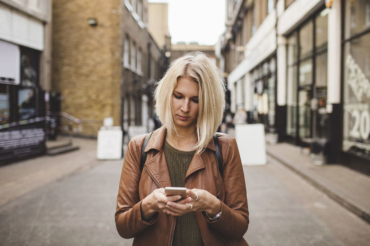 Young woman using phone standing in city